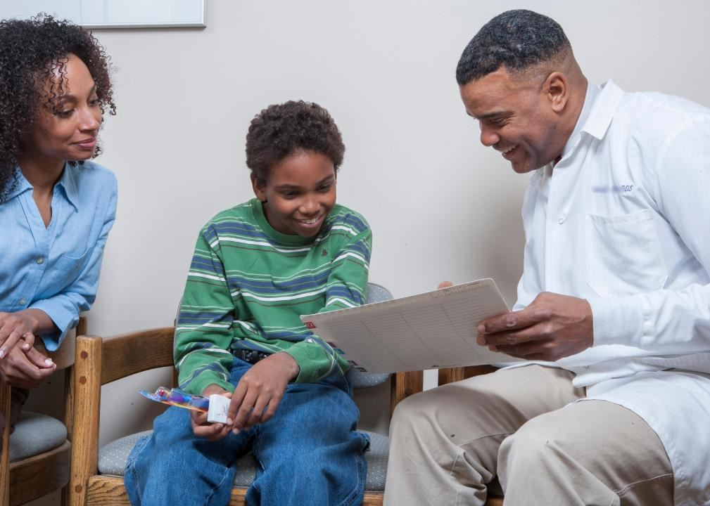 Family at dentist office with dentist showing boy his dental chart