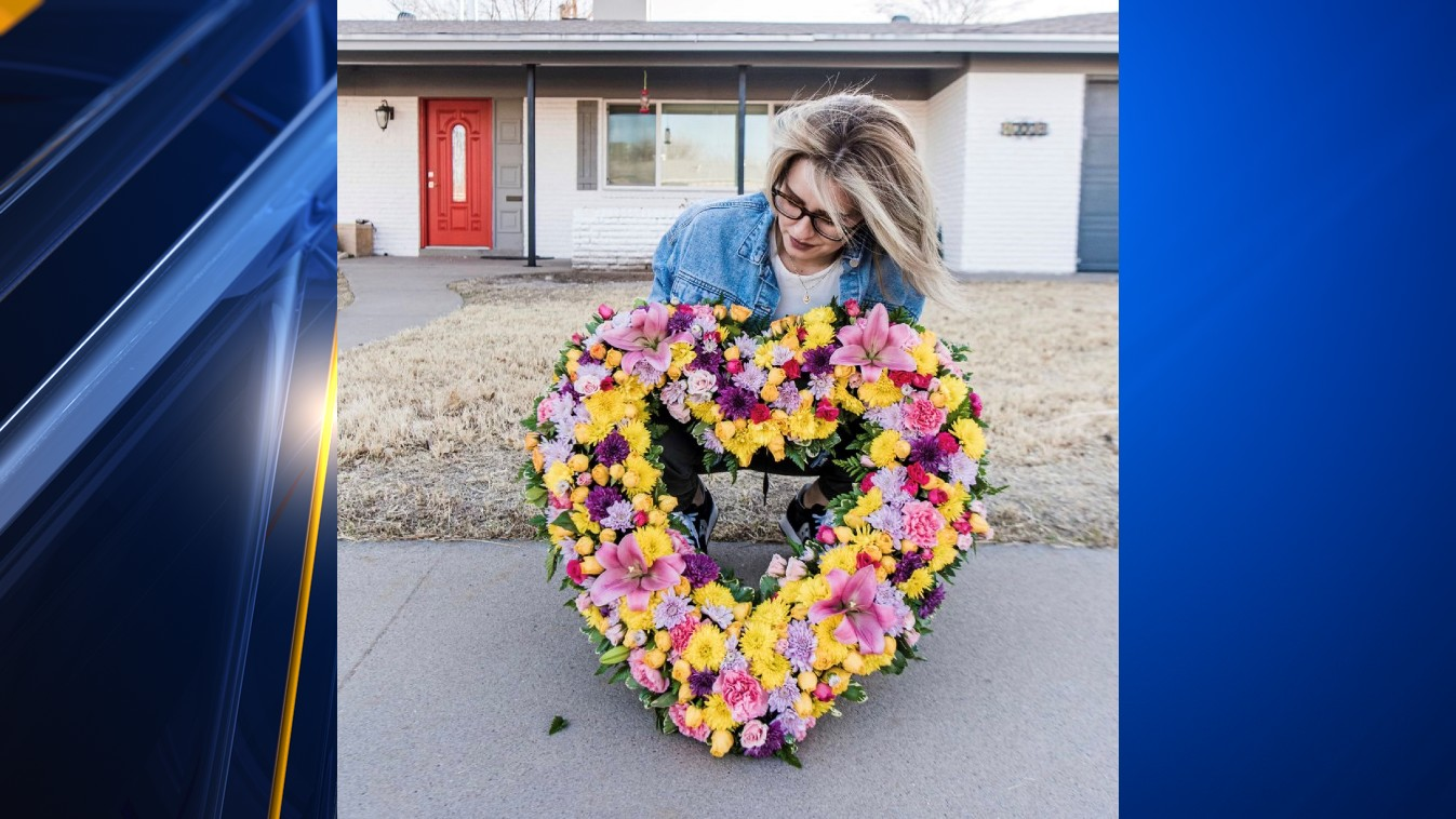 Kaitlyn Urenda-Culpepper holds a heart-shaped wreath made of multi-colored flowers in front of her late mother's home.