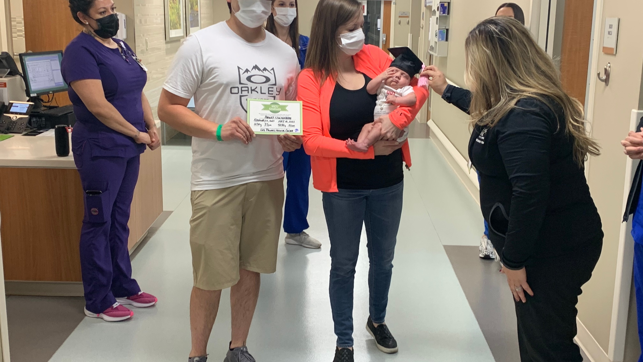 Babies held by their parents are wearing graduation caps with tassels on their wait out of the Neonatal Intensive Care Unit